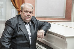 Mature musician playing a white piano Stock Images