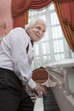 Mature musician playing a white piano Royalty Free Stock Photo
