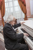 Mature musician playing a white piano Royalty Free Stock Photography