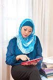 Mature Muslim woman with a book in exhibition hall Royalty Free Stock Photography
