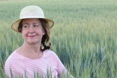 Mature natural woman in the wheat fields.  Stock Photo