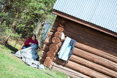 Mature needlewoman sitting in shade and working near house. Mature needlewoman sitting in shade and working near wooden house Stock Photography