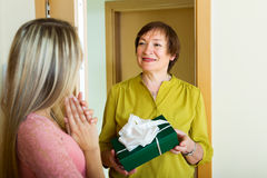 Mature neighbor presenting gift  to  girl Royalty Free Stock Images