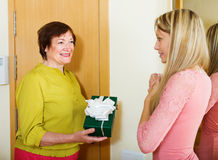 Mature neighbor presenting gift to young girl Stock Photos