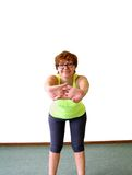Mature, nice woman in yellow shirt doing fitness Royalty Free Stock Image