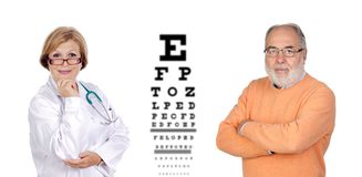 Mature oculist woman checking the view of a senior man stock image