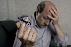 Mature old man on his 60s at home couch alone feeling sad and worried suffering alzheimer disease holding ribbon Stock Photography