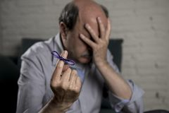 Mature old man on his 60s at home couch alone feeling sad and worried suffering alzheimer disease holding ribbon Stock Image
