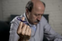 Mature old man on his 60s at home couch alone feeling sad and worried suffering alzheimer disease holding ribbon Royalty Free Stock Photography