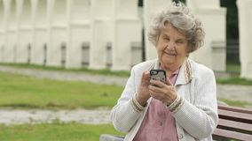 Mature old woman holds silver smart phone outdoors stock video