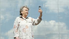 Mature old woman takes photos using a smart phone stock video