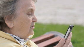 Mature old woman talking on mobile phone outdoors stock footage