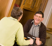 Mature older couple laughing together in kitchen Royalty Free Stock Photos