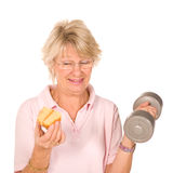 Mature older lady choosing diet or exercise. Mature older lady choosing between diet or exercise, isolated on white background Stock Images