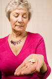 Mature older lady holding tablets or pills Royalty Free Stock Image
