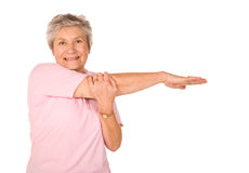 Mature older lady stretching. Mature older lady performing stretching exercises before gym workout royalty free stock image