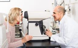Mature optician examinating eyesight with aid of slit lamp Royalty Free Stock Image