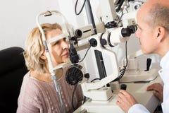 Mature optician examinating eyesight with aid of slit lamp. Positive spanish mature optician examinating eyesight with aid of slit lamp royalty free stock photos