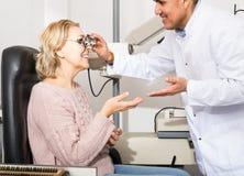 Mature optician examinating eyesight with aid of slit lamp Royalty Free Stock Photos
