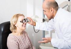 Mature optician examinating eyesight with aid of slit lamp Royalty Free Stock Images