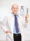 Mature optician holding glasses in his office. Vertical shot of a mature optician holding a pair of glasses and posing in his office in front of an eye chart royalty free stock image