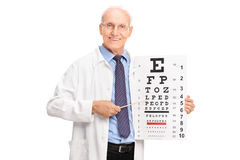 Mature optician pointing on an eyesight test Royalty Free Stock Photo