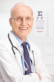 Mature optician posing in his office. Close up on a mature optician posing in his office with an eyesight test in the background royalty free stock image