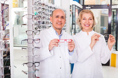 Mature opticians near display with spectacles Royalty Free Stock Images