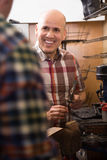 Mature ordinary workman sewing leather boots on stitch lathe in Royalty Free Stock Photography