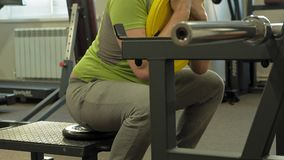 The overweight man does squats with squats with a weight disc for a barbell. Fitness training. Healthy lifestyle concept. A mature overweight man in a green T stock footage