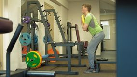 The overweight man does squats with squats with a weight disc for a barbell. Fitness training. Healthy lifestyle concept. A mature overweight man in a green T stock video footage