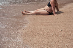 Mature overweight unattractive female body on a beach sand in a two Stock Photography