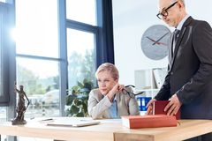 Mature overworked colleagues. At modern office Stock Photos