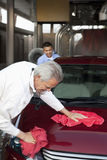 Mature owner and young employee wiping vehicle with cloth in car wash Stock Image