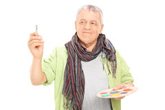 Mature painter holding paintbrush and color pallet. Isolated on white background royalty free stock photo