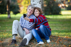Mature pair making selfie with cellphone in autumn park Royalty Free Stock Photo