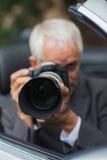 Mature paparazzi taking picture Stock Photos