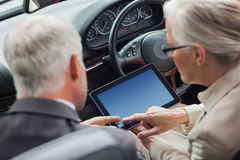 Mature partners working together on tablet in classy convertible Stock Photos