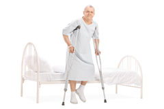Mature patient with crutches getting out of bed. Full length portrait of a mature patient with crutches getting out of bed isolated on white background Royalty Free Stock Images