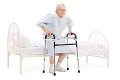 Mature patient getting up from bed with walker Stock Photos