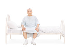 Mature patient in a hospital gown sitting on a bed Royalty Free Stock Photography