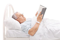 Mature patient reading book in a hospital bed Royalty Free Stock Image