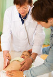 Mature pediatrician doctor examing baby Stock Image