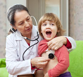 Mature pediatrician doctor examining baby Stock Image
