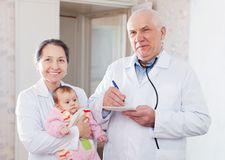 Mature pediatrician doctors with  baby Royalty Free Stock Photo