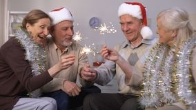 Mature people lighting sparklers, friends celebrating New Year and Christmas. Stock footage stock footage