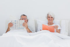 Mature people reading in bed Stock Images
