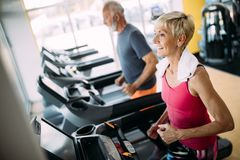 Senior people running in machine treadmill at fitness gym club royalty free stock photo