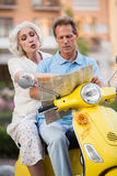 Mature people sitting on scooter. Man with map beside woman. We should turn here. I don't know this town Stock Image