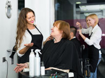 Mature person  talking about cuts hair Royalty Free Stock Photography